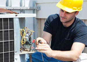 HVAC technician repairing an AC unit